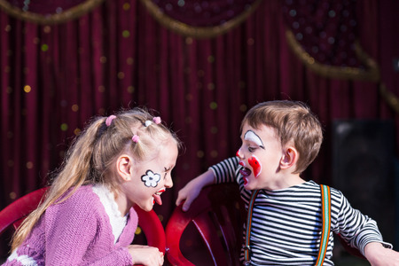 Cute funny boy and girl with painted faces acting as a couple with communication problems, during a theatrical performance photo
