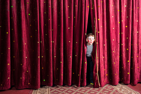 Excited little boy on stage peering out from between the curtains in his costume and makeup waiting for the performance to begin