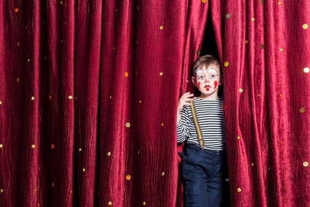 彼の衣装とメイクでブルゴーニュのカーテンの間から外をピアリングを開始するパントマイムの演技でせっかちな少年の笑顔 写真素材