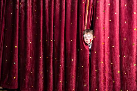 sipario chiuso: Divertimento ragazzino nel trucco che aspetta la sua stecca recitazione poking la testa fuori tra le tende, mentre aspetta di fare il suo ingresso sul palco durante la performance