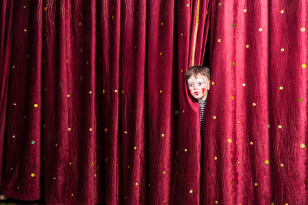 stage costume: Fun little boy in makeup waiting for his acting cue poking his head out between the curtains as he waits to make his entrance on stage during the performance