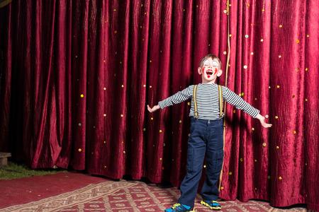 Schattige kleine jongen zingen op het podium tijdens een toneelstuk staat met uitgestrekte armen in zijn kostuum en make-up in de voorkant van de bordeaux gekleurde gordijn Stockfoto