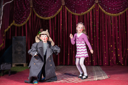 Children Wearing Clown Make Up and Costumes Having Fun and Performing on Stage with Red Curtain