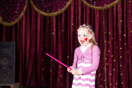girl in red dress: Smiling Blond Girl Wearing Clown Make Up and Striped Dress Standing on Stage Holding Over Sized Pink Comb in front of Red Curtain Stock Photo