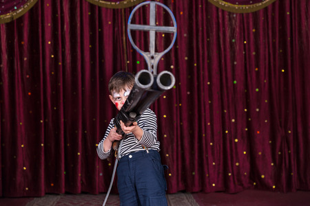 iron curtain: Young Boy Dressed as Clown Holding Large Gun with Iron Sight at End of Barrel, Standing on Stage with Red Curtain