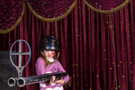 over sized: Tough Looking Girl with Face Painted Wearing Over Sized Helmet Holding Large Double Barreled Gun on Stage with Red Curtain