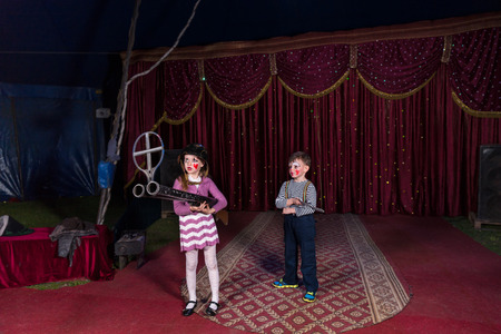 blunderbuss: Boy and Girl Dressed as Clowns Standing on Stage Holding Large Double Barreled Shot Gun
