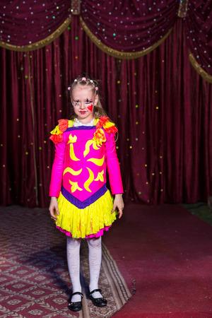 pantomima: Ni�a adorable en un traje de color rosa y amarillo con el pelo rubio atado con perlas de hacer su debut en el escenario durante una obra de teatro o pantomima de pie delante de las cortinas Foto de archivo