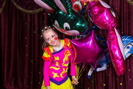stage costume: Smiling Blond Girl Wearing Colorful Costume and Make Up Holding Bunch of Foil Balloons Standing on Stage with Red Curtain Stock Photo