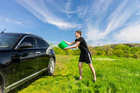 coachwork: Young Man Washing Black Luxury Vehicle in Grassy Green Field on Bright Sunny Day with Blue Sky, Tossing Bucket of Water Onto Side of Car Stock Photo