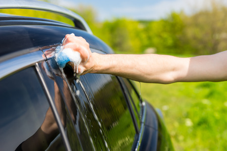 coachwork: Close Up of Man Washing Windows of Black Luxury Vehicle with Soapy Sponge in Green Field on Bright Sunny Day