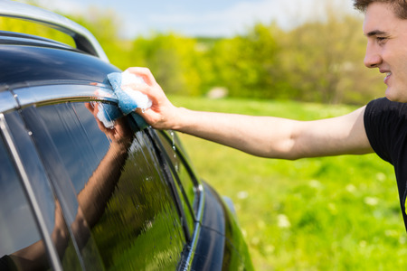 coachwork: Close Up of Young Man Washing Windows of Black Luxury Vehicle with Soapy Sponge in Green Field on Bright Sunny Day