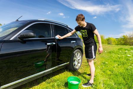 autolavaggio: Figura intera dell'uomo lavaggio auto con insaponata spugna in verde campo erboso su luminosa giornata di sole con cielo blu Archivio Fotografico