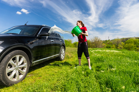 shampooing: Young Woman Washing Black Luxury Vehicle in Grassy Green Field on Bright Sunny Day with Blue Sky, Tossing Bucket of Water Onto Side of Car Stock Photo