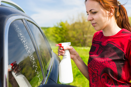 woman squirt: Woman Wearing Red Shirt Cleaning Car Windows with Spray Bottle Cleaner in Green Field on Bright Sunny Day