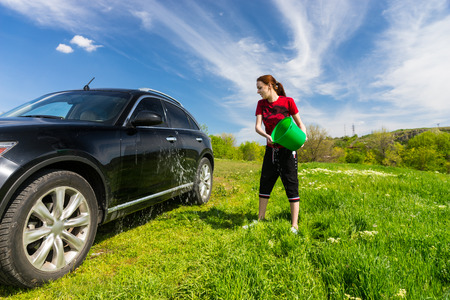 tossing: Young Woman Washing Black Luxury Vehicle in Grassy Green Field on Bright Sunny Day with Blue Sky, Tossing Bucket of Water Onto Side of Car Stock Photo