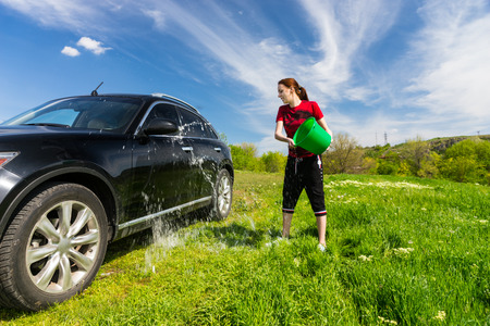 coachwork: Young Woman Washing Black Luxury Vehicle in Grassy Green Field on Bright Sunny Day with Blue Sky, Tossing Bucket of Water Onto Side of Car Stock Photo
