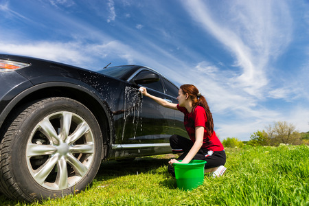 wash car: Woman with Green Bucket Washing Black Luxury Vehicle with Soapy Sponge in Green Field on Bright Sunny Day with Blue Sky Stock Photo