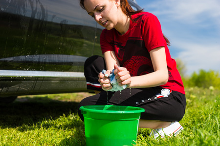 soapy water: Close Up of Woman Wearing Red T-Shirt Washing Black Vehicle in Field with Sponge, Crouching Next to Green Bucket Filled with Soapy Water Stock Photo
