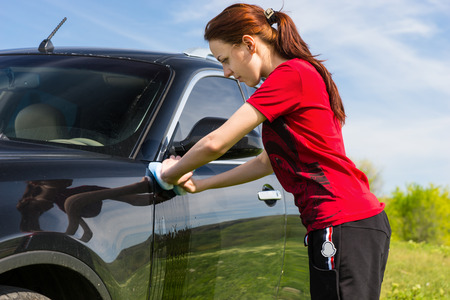 auburn hair: Young Woman with Long Auburn Hair and Wearing Red Shirt Washing Black Luxury Vehicle with Sponge in Green Field on Sunny Day Stock Photo