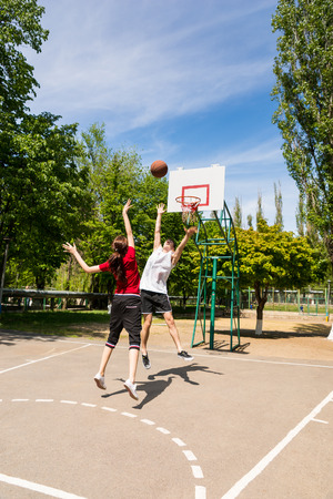 camaraderie: Young Athletic Couple Playing Basketball Together - Man in front of Net Blocking Womans Shot on Outdoor Court in Lush Green Park Stock Photo