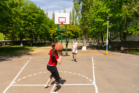 camaraderie: Young Athletic Couple Playing Basketball Together - Man Watching as Woman Takes Shot from Top of Key on Outdoor Court in Lush Green Park