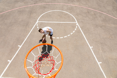 High Angle View from Backboard of Young Athletic Man Dribbling Ball on Outdoor Basketball Court and Looking Up at Net on Sunny Day photo