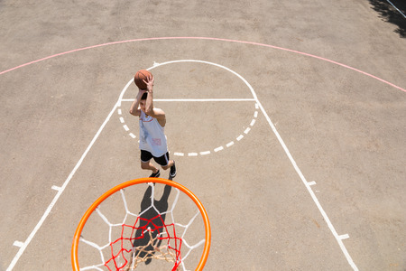High Angle View from Backboard of Young Athletic Man Taking Shot on Net on Outdoor Basketball Court photo
