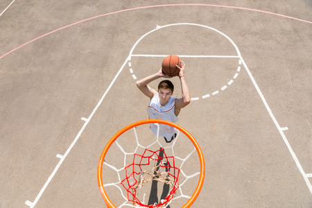 High Angle View from Backboard of Young Athletic Man Making Jump Shot on Net on Outdoor Basketball Court photo