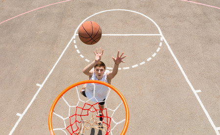 High Angle View from Backboard of Young Athletic Man Taking Lay Up Shot on Net on Outdoor Basketball Court photo