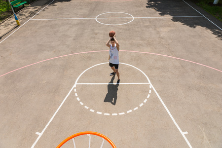outdoor basketball court: High Angle View from Backboard of Young Athletic Man Taking Shot on Net from Free Throw Line in Key on Outdoor Basketball Court
