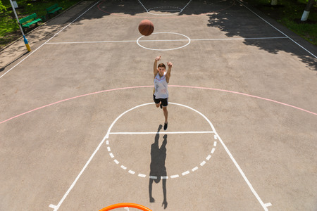 outdoor basketball court: High Angle View from Backboard of Young Athletic Man Taking Shot from Free Throw Line on Key of Outdoor Basketball Court on Sunny Day