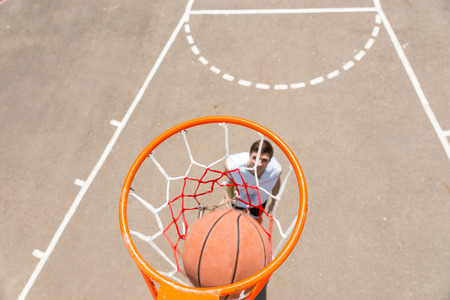 outdoor basketball court: High Angle View from Backboard of Young Athletic Man Making Shot on Net on Outdoor Basketball Court on Sunny Day