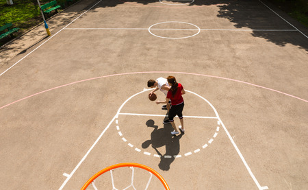 High Angle View from Backboard of Young Athletic Couple Playing Basketball on Outdoor Court on Sunny Day photo