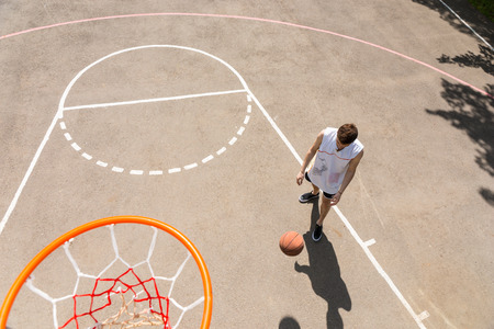 dribbling: High Angle View of Young Man Playing Basketball, View from Above Hoop of Man Dribbling Basketball