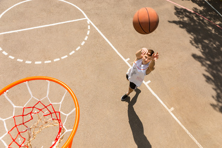 High Angle View of Young Man Playing Basketball, View from Above Hoop of Man Shooting Basketball photo