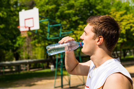 tomando refresco: Cabeza y hombros Vista de hombre joven bebiendo agua de botella, Hacer una pausa para refrescarse e hidratación en la cancha de baloncesto Foto de archivo