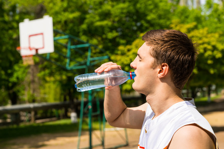tomando agua: Cabeza y hombros Vista de hombre joven bebiendo agua de botella, Hacer una pausa para refrescarse e hidratación en la cancha de baloncesto Foto de archivo