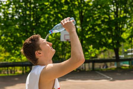 tomando refresco: Cabeza y hombros Vista del Hombre Joven Atlético agua de colada de la botella en la cara, Hacer una pausa para refrescarse e hidratación en la cancha de baloncesto