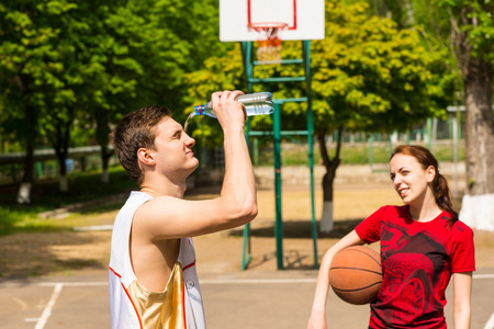 Young Athletic Couple Taking a Refreshing Break on Basketball Court, Woman Looking On As Man Empties Water Bottle Onto Face Stock Photo