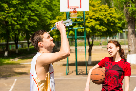 empties: Young Athletic Couple Taking a Refreshing Break on Basketball Court, Woman Looking On As Man Empties Water Bottle Onto Face Stock Photo
