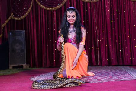 Full Length of Exotic Dark Haired Dancer Kneeling on Stage Next to Large Snake