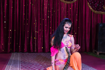 charmer: Exotic Dark Haired Snake Charmer Dancer Wearing Bright Colored Costume Kneeling on Stage with Large Snake with Red Curtain in Background