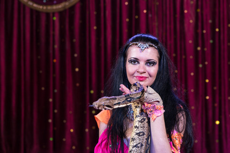 circus performers: Portrait of Exotic Dark Haired Snake Charmer Holding Large Snake on Stage with Red Curtain in Background and Copy Space Stock Photo