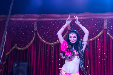 sexy girl dance: Waist Up of Exotic Dark Haired Belly Dancer with Large Snake Around Shoulders, Dancing with Arms Over Head on Stage with Red Curtain in Background