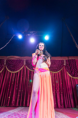 orange snake: Full Length Low Angle View of Exotic Female Belly Dancer Wearing Bright Pink and Orange Costume with Large Snake Wrapped Around Shoulders Backlit by Bright Spotlights on Stage Stock Photo