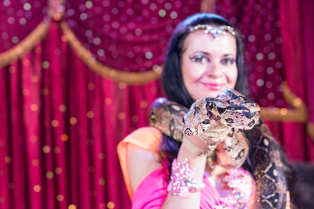 snake head: Head and Shoulders Close Up Portrait of Exotic Dark Haired Snake Charmer Wearing Large Snake Around Shoulders on Stage with Red Curtain Stock Photo