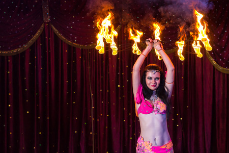 above head: Exotic Female Fire Dancer Wearing Bright Pink Costume Twirling Flaming Apparatus Above Head on Stage with Red Curtain Stock Photo