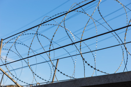 razor wire: Detail of Razor Wire on Top of Security Fence with Blue Sky in Background