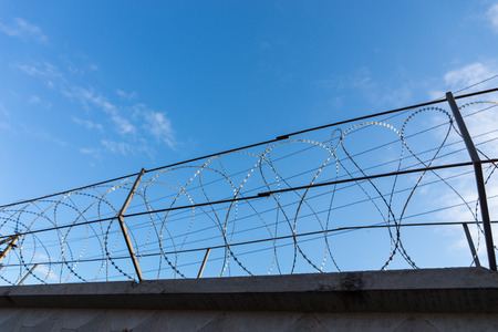 razor wire: Razor Wire Along Top of Security Fence at Prison or Other High Security Facility with Sunny Blue Sky in Background Stock Photo